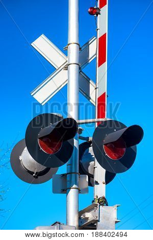 Closeup of a railroad gate and signal against a bright blue sky