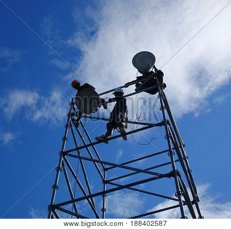 Workers Set Up Powerful Floodlights