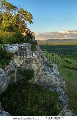 Tourist on the stone throne on the top of the Cave city Bakla in Bakhchysarai Raion, Crimea.