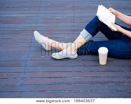 Woman with book sitting on wooden floor