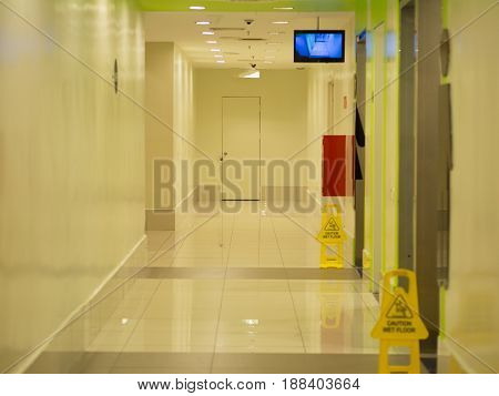 empty long corridor in shopping mall building in front of toilet.