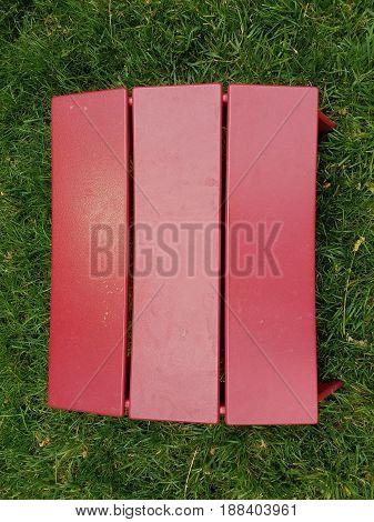 small dark red foot stool on green grass
