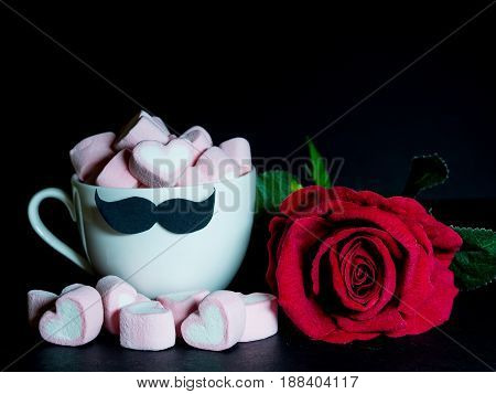 Father's day concept. with red rose and sweet marshmallow in the shape of heart in a tea cup with black Mustache on dark background