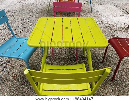 yellow table with brightly colored chairs outdoors