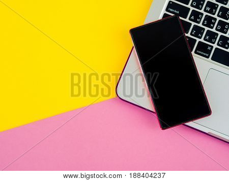 Top view of smartphone on laptop on pink and yellow background