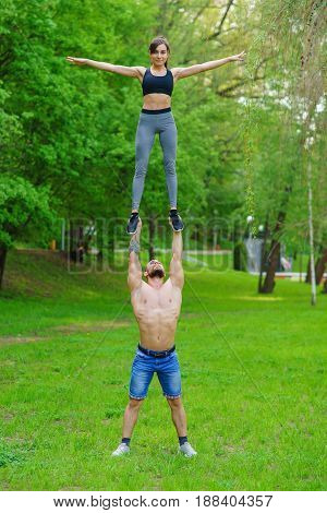 The guy and the girl are engaged in sports, aerial gymnastics in the park. The guy tosses the soup high into the air and catches it.