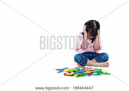 Asian child hold the head with hand while play toy wood blocks. Sad girl crying and showing moody behavior. Isolated on white background. Educational toys for kindergarten child. Free form copy space.