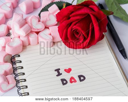 Father's day concept. I LOVE DAD message write on note book with red rose glasses and two red hearts on white background