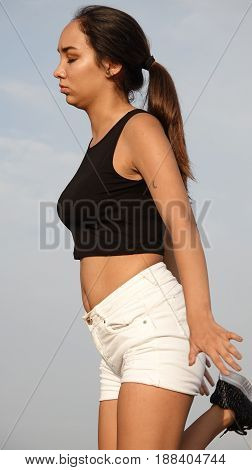 Stretching Pretty Female Teenager on Isolated Blue Sky Background