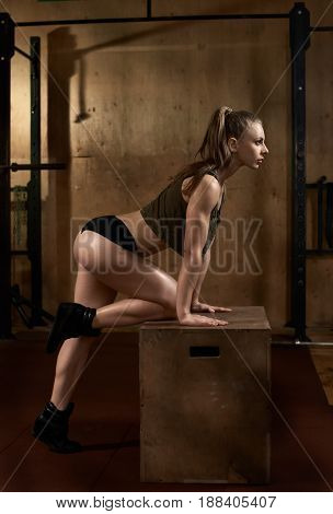 Side-view portrait of strong muscular woman exercising with box