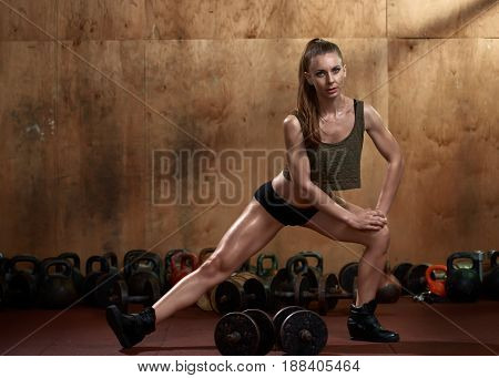 Athletic fit woman stretching before training with dumbbells