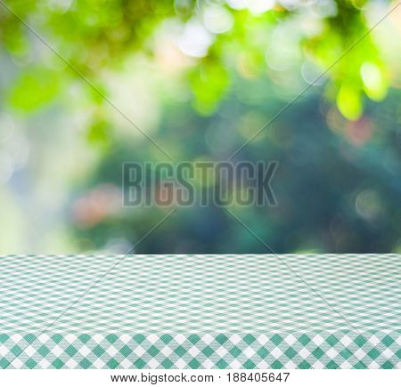 Empty table with green tablecloth over blur garden and bokeh background for food and product display montage spring and summer season