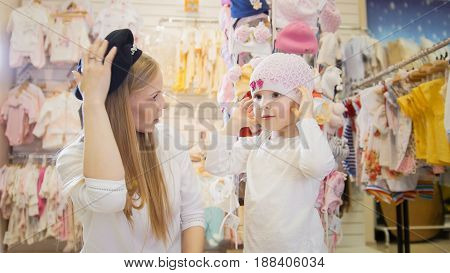A young mother with a young daughter trying on beautiful hats in the children's clothing store
