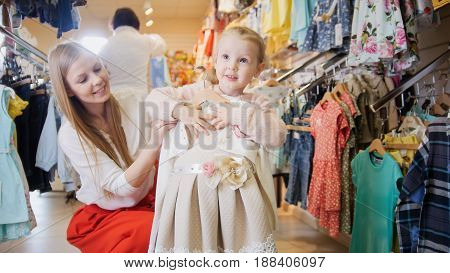 Shopping for kids - little girl with mom to buy beige summer dress children's clothing store.