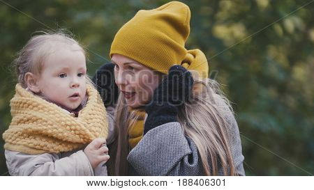 Baby blonde child girl with her mommy plays in autumn park, close up, telephoto