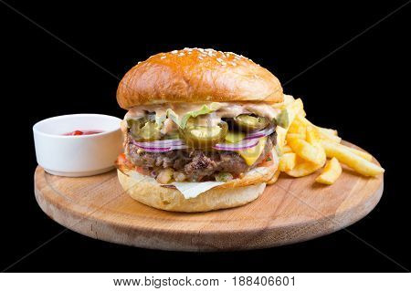 Burger with french fries on a round wooden board