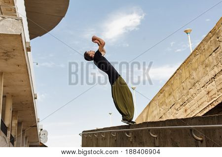 Young man back flip. Parkour in the urban space. Sports in the city. Sport Activities outdoors.