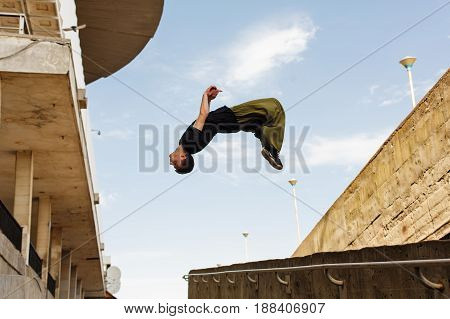 Young man back flip. High point of the coup. Parkour in the urban space. Sports in the city. Sport Activities outdoors.