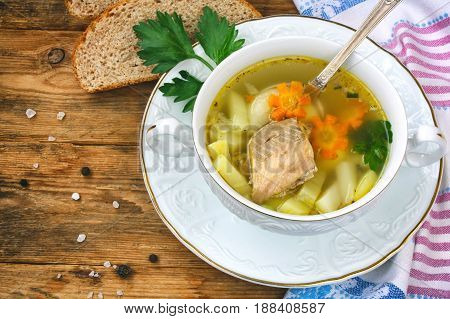 Salmon fish soup with carrots and potatoes in a white bowl on a plate slices of bread towel on a wooden table closeup