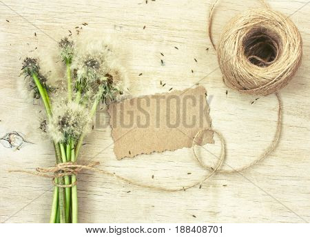 bouquet of dandelions blowing blank paper tag coil of rope on a wooden table rustic style top view flat lay