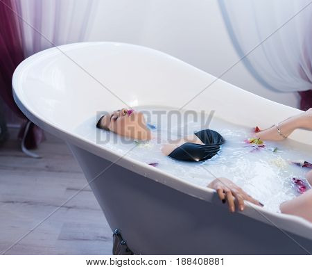 Woman in bath. Sexy brunette woman relaxing in hot milk bathtube with flowers. she is wearing black sexual lingerie. Spa satisfaction of woman in bath
