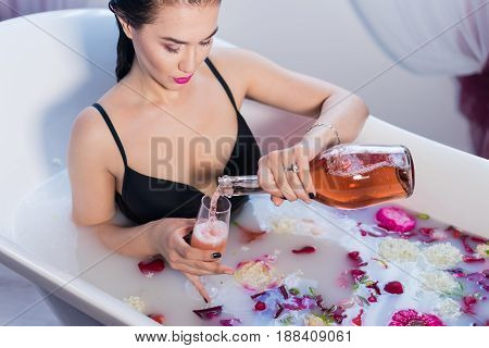 Sexy brunette woman relaxing in a hot bath wearing black sexual lingerie. She is pouring champagne to wineglass