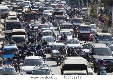 KATHMANDU NEPAL - OCTOBER 25 2016 : Traffic moves slowly along a busy road in Kathmandu Nepal. Crowded traffic jam road in city