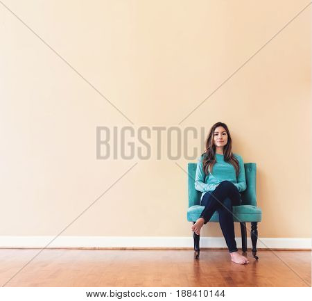 Young Latina Woman Sitting In A Chair