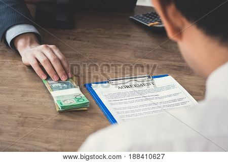 Businessman giving money (Australian dollars) exchanging with agreement paper - bribery and corruption concepts