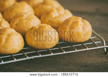 Homemade cream puffs or eclaire filled with vanilla custard cream on cooling rack. Golden choux cream on rustic wood table. Cream puffs already baked. Cream puffs or choux cream or eclairs. French pastry : cream puffs or choux cream.