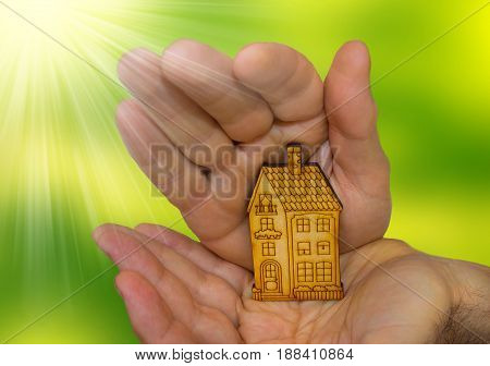 The bright picture of man holding wooden house on green. Concept of dream