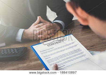 Business partners making agreement with hidden money on the table - bribery corruption and loan concepts