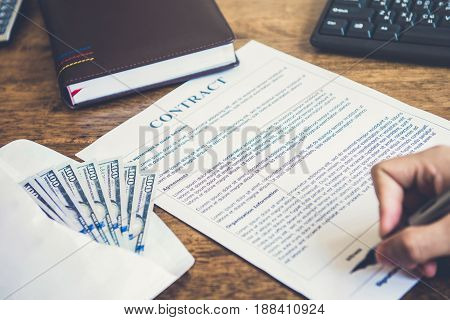 A man signing contract with money on the table - loan bribery and corruption concepts
