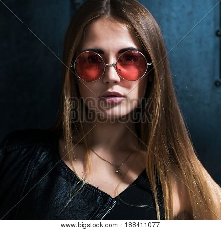 Close up face portrait of beautiful Caucasian young woman with loose hair in fashionable pink round sunglasses looking at camera.
