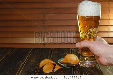 A large glass of beer and potato chips. On the wooden table stands just poured a glass of beer. High foam in the glass. Light beer. White foam on the beer. Men's hand hit the table.