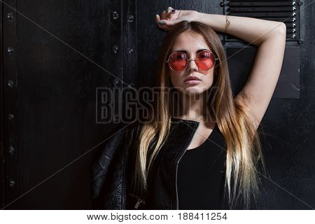 Full face portrait of fashion model in sunglasses with loose long fair hair posing in black surrounding.
