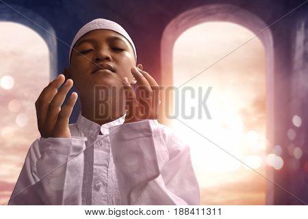 Asian muslim kid praying to god in mosque