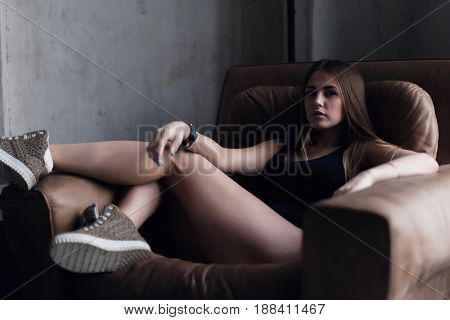 Confident pretty girl sitting in big armchair wearing stylish sneakers and tank top looking at camera in dark room.