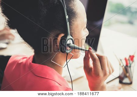 Black businesswoman wearing microphone headset working in the office back view