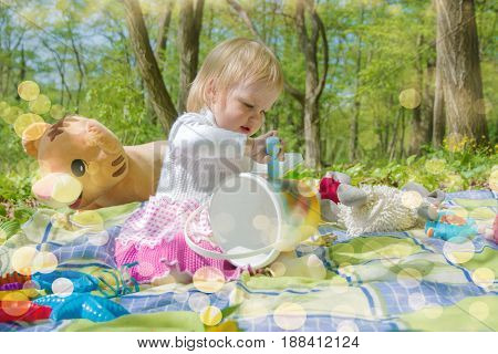 little girl playing in the park with a bucket and crayons on a sunny day