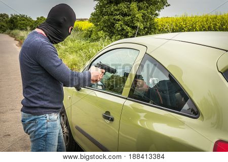 Male thief or terrorist is pointing a pistol on the driver he trying to steal a car
