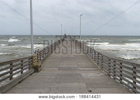 Long wood and concrete fishing pier with benches and light poles extending out into the ocean waves as they crash onto the beach.