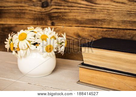 bouquet of white daisies and books on wooden background