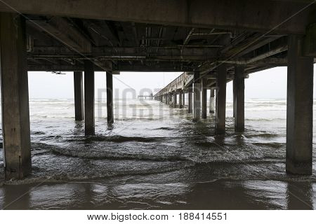 Ocean waves rolling and breaking onto the beach sand under the wood supports of a long pier that stretches to the distant horizon on a bleak cloudy day.