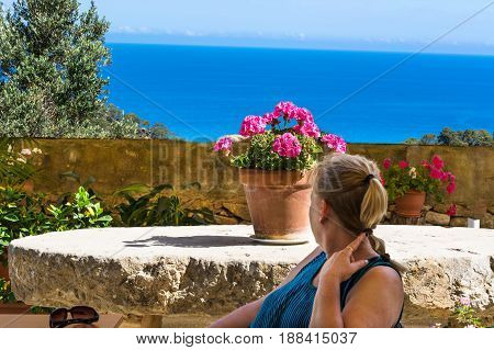 Woman sitting in a restaurant and looking at the sea