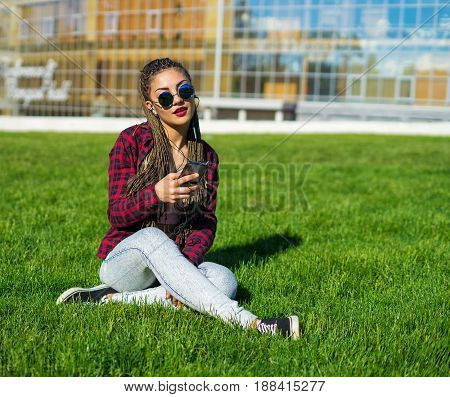 Young beautiful girl with zizi cornrows dreadlocks listening to music sitting on the lawn