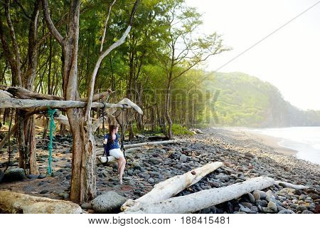 Young Female Tourist Relaxing On A Handmade Swing On Rocky Beach Of Pololu Valley On Big Island Of H