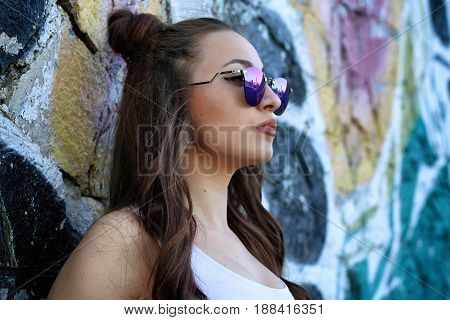 Beautiful girl dressed in a street style outfits posing in front of wall full of graffitis. Wearing white top and blue sunglasses.