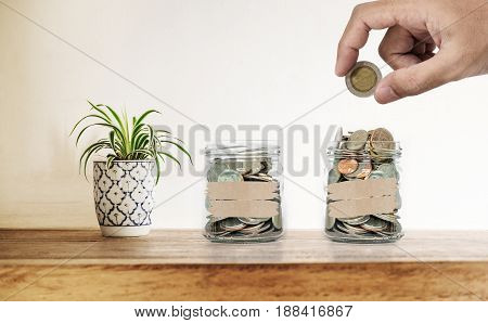 Hand putting coin in glass bottles, with  decoration plant on wooden desk, Saving money , investment and economize concepts