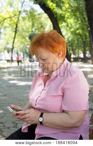 elegantly dressed elderly woman is calling by phone in the city park.